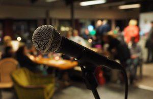 Nærbilde av mikrofon med publikum bak