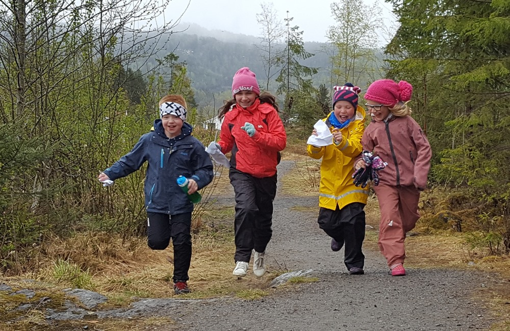 4 glade barn som løper i skogen. Foto.