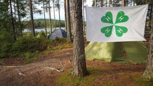4H leir i skogen med telt og logo. Foto.