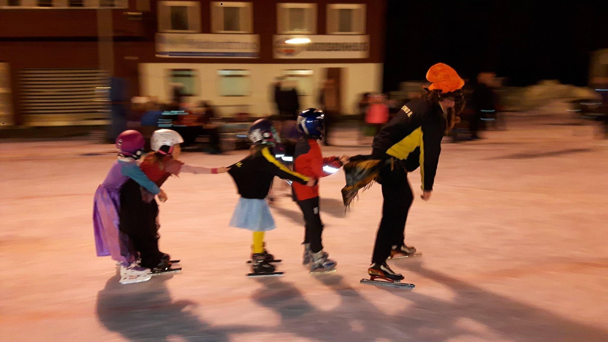 Fire barn som går på skøyter i rekke bak en voksen. Foto.