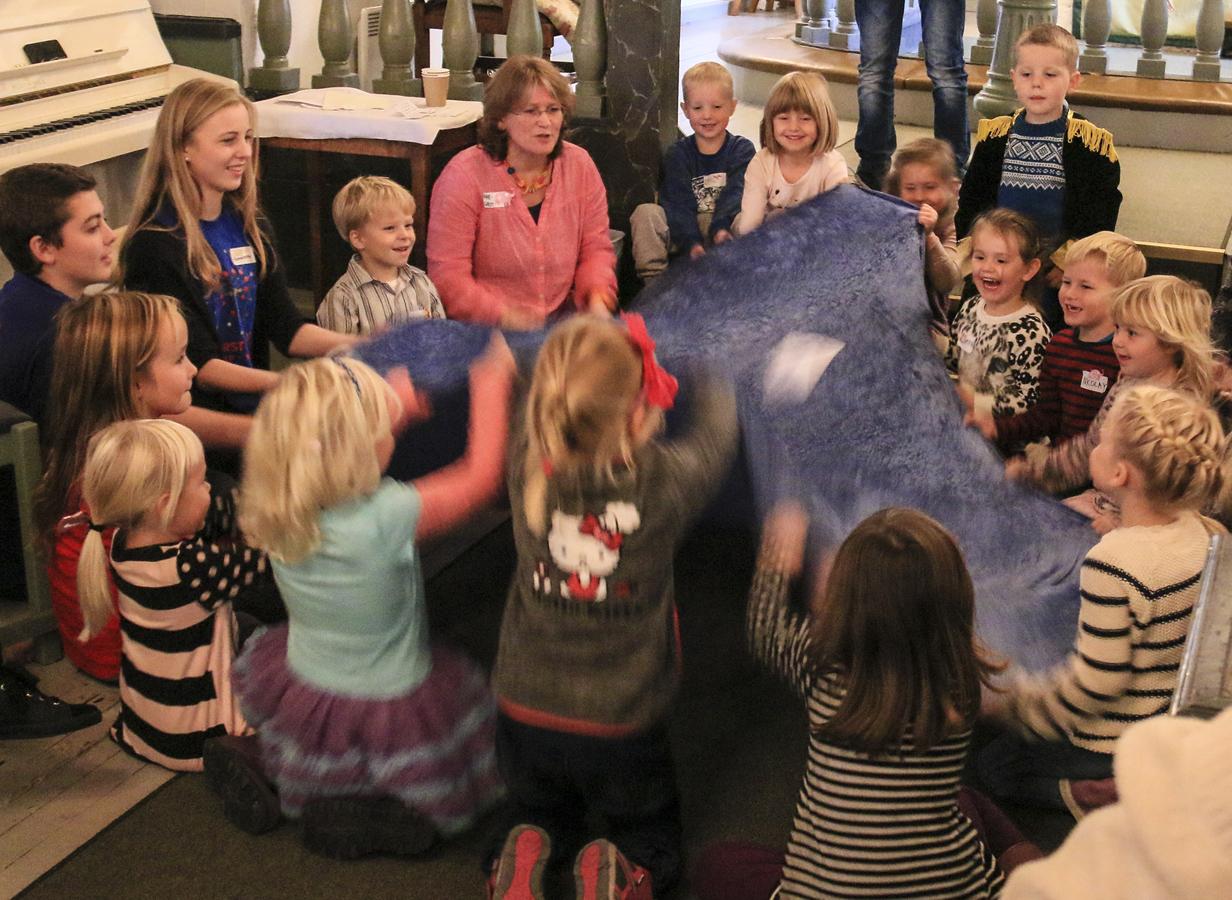 Barn som står i sirkel rundt en voksen. Foto.
