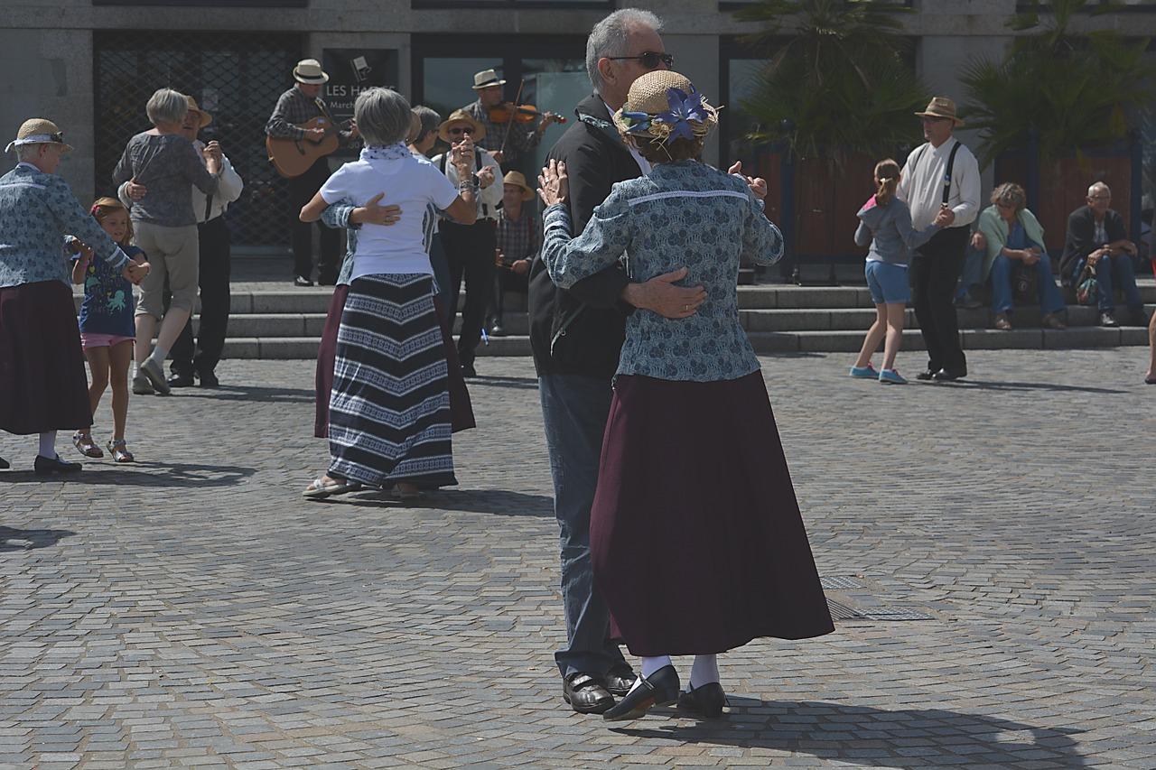 Folk som danser i par ute.