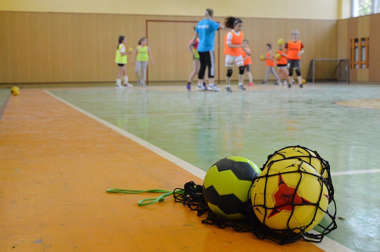 Håndball i nett med spillere i bakgrunn. Foto.