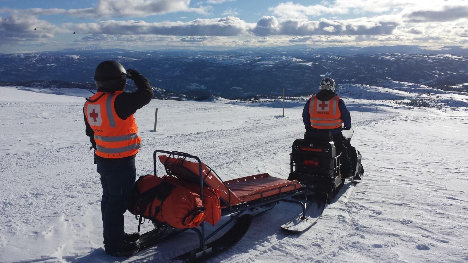 Tp personer i Røde kOrs hjelpetjeneste på skuter i fjellet. Foto.